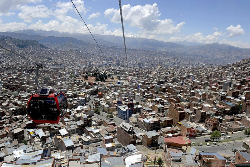 A cable-car is seen over La Paz, considered the highest project of its kind moving at over 4,000 meters above sea level, on October 10, 2014, two days before six million Bolivians are expected to vote on the general and presidential election of October 12. Both routes over the Bolivian capital have a combined capacity to seat 18,000 users an hour. AFP PHOTO/JORGE BERNAL (Photo credit should read JORGE BERNAL/AFP/Getty Images)