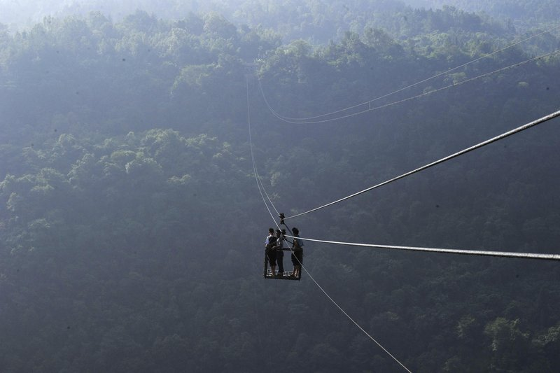 "Mandatory Credit: Photo by Quirky China News/REX (1840812e) The cable ropeway in operation Cable ropeway suspended between cliffs is mountain village's only access to the outside, Yushan village, Hubei Province, China - Sep 2012 *full story: http://www.rexfeatures.com/nanolink/hyt6 The ropeway between Yushan village and the outside world is a simple affair. A pair of thick cables are strung between two high cliff faces with a steel cage suspended below to carry people and goods in and out of the village. Yushan village has a population of just over 200 people and the only access to the outside world is via this 'sky road'. The ropeway was built in 1997; before that villagers faced a walk of several days to get to the next nearest village. The ropeway, which is powered by a diesel engine, is 1,000 meters long and 400 meters above the valley floor. Zhang Xinjian has been maintaining the ropeway for the past 15 years. He comments: ""I started to work at this spot since the rope was set up. No one would take the job""."